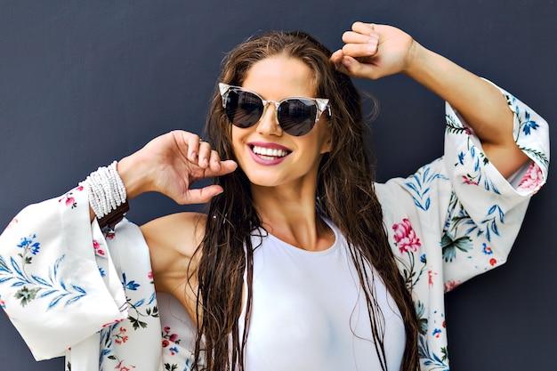 Schließen sie herauf mode-sommerporträt der atemberaubenden brünettenfrau, die am grauen hintergrund, lange nasse haare nach dem schwimmen aufwirft Kostenlose Fotos