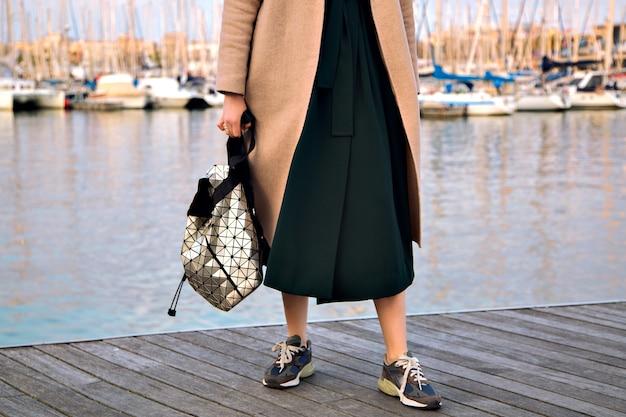 Schließen sie herauf modedetails der trendigen frau, die elegantes kleid moderne trendige turnschuhe und rucksack mit elegantem kaschmirmantel trägt, posiert an der strandpromenade, zwischensaison, weiche pastellfarben. Kostenlose Fotos