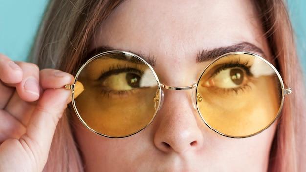 Schließen sie herauf modell mit gelben gläsern Kostenlose Fotos