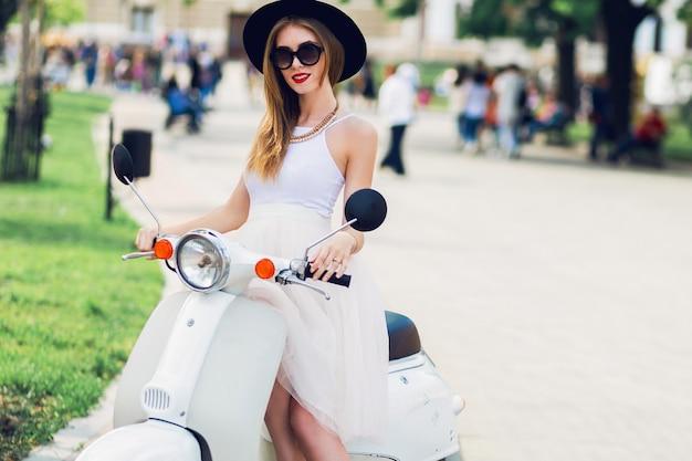 Schließen sie herauf modeporträt der jungen blonden frau im weißen tüllrock und in den schwarzen absätzen, die auf vintage roller sitzen. Kostenlose Fotos