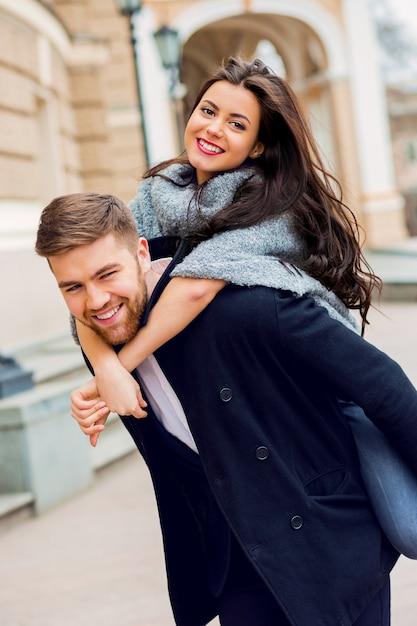 Schließen sie herauf modeporträt des jungen stilvollen glamourmädchens und des verliebten kerls. paar, das die straße im sonnigen herbst hinuntergeht. warme herbstfarben. trägt ein schwarzes trendiges outfit. Kostenlose Fotos