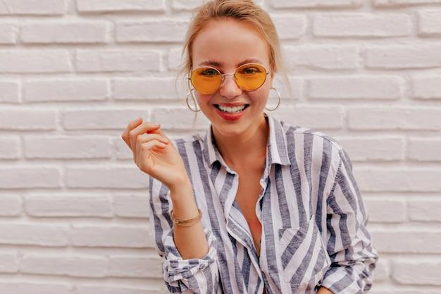 Schließen sie herauf porträt der attraktiven frau mit wunderbarem lächeln, das orange brille und abgestreiftes hemd trägt Kostenlose Fotos