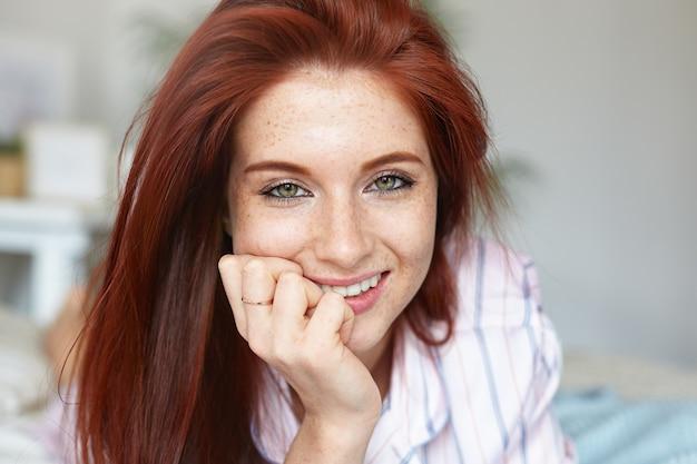 Schließen sie herauf porträt der attraktiven rothaarigen jungen kaukasischen frau mit den grünen augen und der perfekten sommersprossigen haut, die morgen im bett verbringen und pyjamas tragen. schönheit, jugend, freizeit, menschen und lebensstil Kostenlose Fotos
