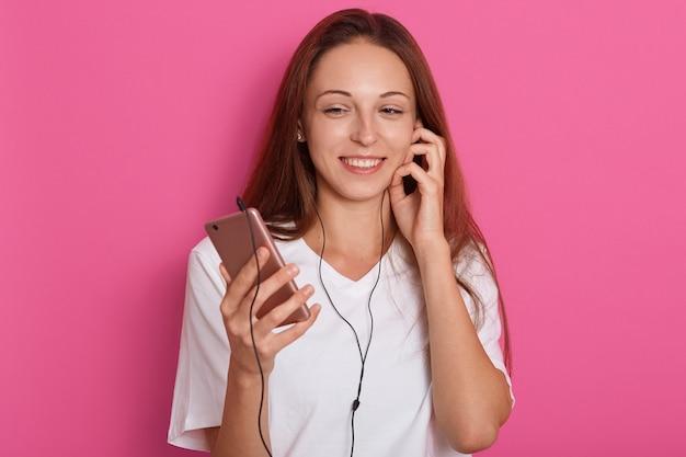 Schließen sie herauf porträt der frau, die musik unter verwendung des smartphones hört. frische energetische glückliche kaukasische brünette über rosa Kostenlose Fotos