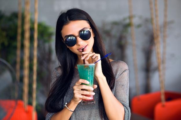 Schließen sie herauf porträt der glücklichen hübschen brünetten frau, die leckeren kalten cocktail, stilvolles outfit und verspiegelte sonnenbrille trinkt, genießen sie ihr wochenende, partyzeit. Kostenlose Fotos