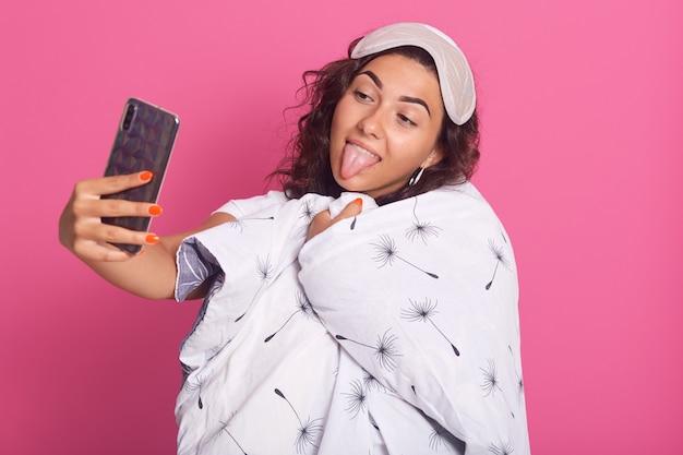 Schließen sie herauf porträt der glücklichen weiblichen eingewickelten weißen decke mit löwenzahn, zeigt ihre zunge, selfie machend Kostenlose Fotos