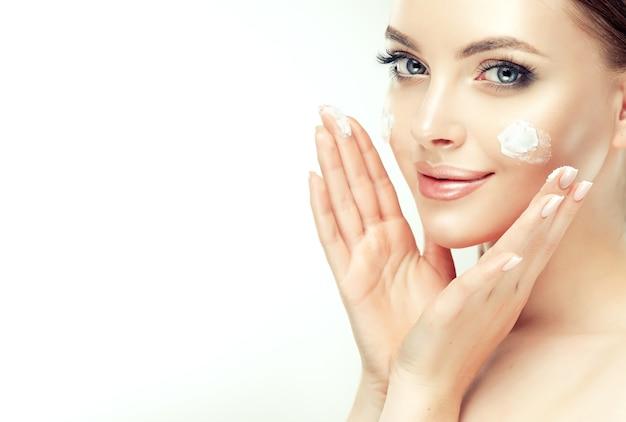 Schließen sie herauf porträt der herrlichen, jungen, braunhaarigen frau mit flecken der kosmetischen creme Premium Fotos