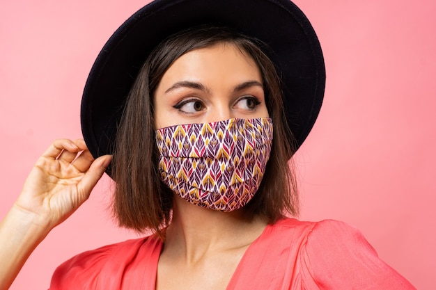 Schließen sie herauf porträt der hübschen frau gekleideten schützenden stilvollen gesichtsmaske. trägt schwarzen hut und sonnenbrille. posieren über rosa wand Kostenlose Fotos