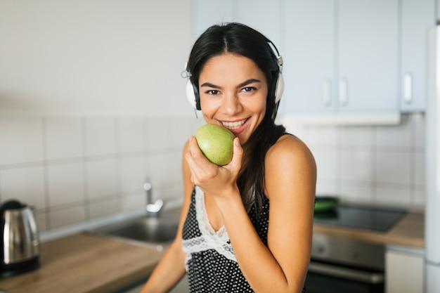 Schließen sie herauf porträt der jungen attraktiven frau, die in der küche am morgen kocht, apfel isst, lächelt, glückliche positive hausfrau, gesunden lebensstil, musik auf kopfhörern hört, lacht, weiße zähne Kostenlose Fotos