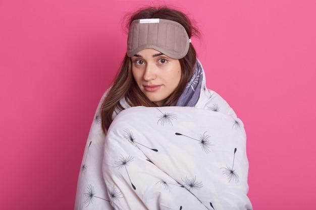 Schließen sie herauf porträt der verschlafenen frau mit schlafmaske auf kopf und tragende decke Kostenlose Fotos