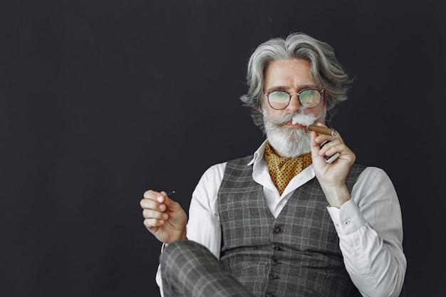 Schließen sie herauf porträt des grinsenden altmodischen mannes. großvater mit zigarre und whisky. Kostenlose Fotos