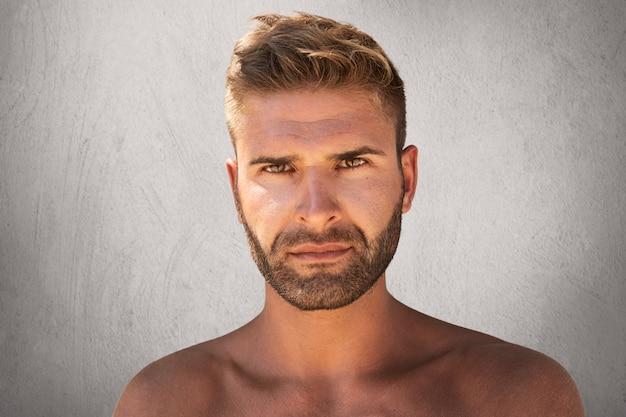 Schließen sie herauf porträt des gutaussehenden mannes mit den dunklen augen, der borste und der trendigen frisur, die nackt sind Kostenlose Fotos