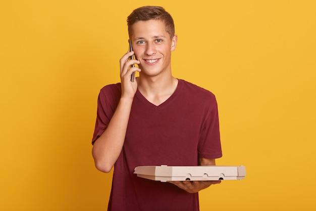 Schließen sie herauf porträt des jungen auslieferungsmannes, der pizzaschachteln in den händen hält und konversation über handy hat, lässig tragend, lächelnd in die kamera schauend, isoliert auf gelb posierend. Kostenlose Fotos