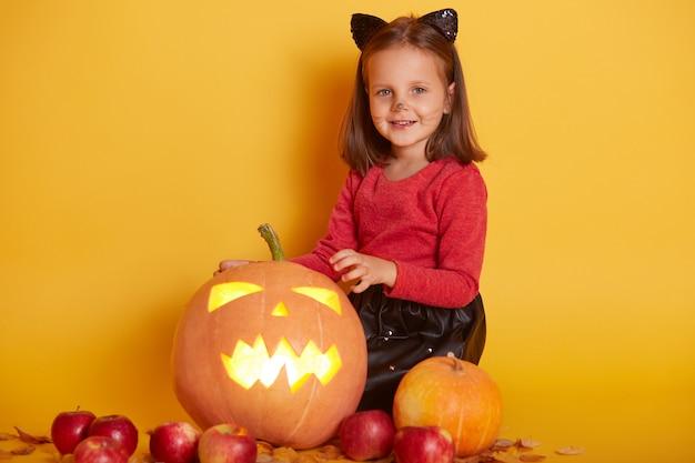 Schließen sie herauf porträt des niedlichen kleinen mädchens mit dunklem haar, das rotes hemd in der herbstlandschaft mit kürbissen trägt Premium Fotos