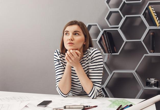 Schließen sie herauf porträt des schönen jungen europäischen dunkelhaarigen weiblichen designers, der am tisch im gemeinsamen arbeitsraum sitzt, mit verträumtem ausdruck beiseite schaut und sich um das treffen von morgen sorgen macht. Kostenlose Fotos
