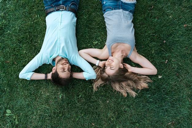 Schließen sie herauf porträt des sorglosen paares, das auf gras zusammen in der liebe liegt Kostenlose Fotos