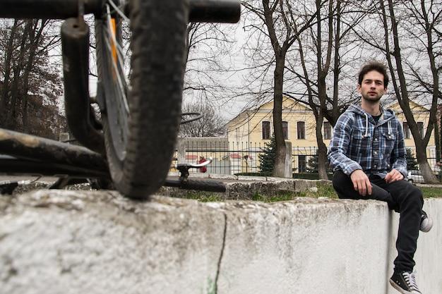Schließen sie herauf porträt des stilvollen hübschen hippie-kerls, der am stadtpark nahe seinem fahrrad sitzt Premium Fotos