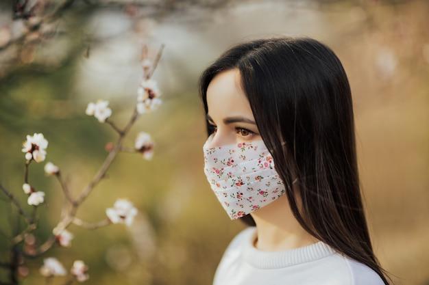 Schließen sie herauf porträt des zarten mädchens in einer weißen bluse unter einem blühenden aprikosenbaum mit einer maske mit blume Premium Fotos
