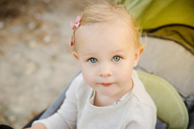 Schließen sie herauf porträt eines netten kleinen mädchens in einem spaziergänger. Premium Fotos