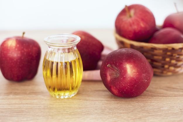 Schließen sie herauf roten apfelfrucht- und apfelessigsaft Premium Fotos