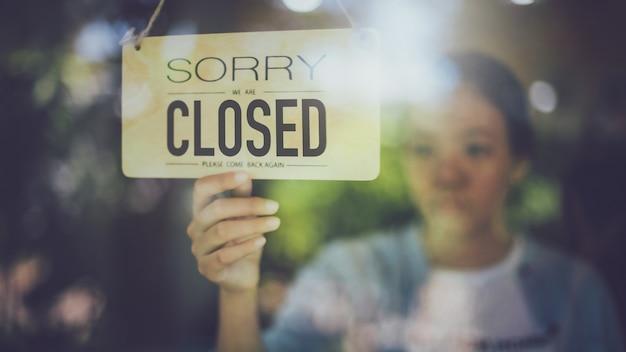 Schließen sie herauf schuss der frauenhand, die nahes schild an der glastür im kaffeehaus dreht. Premium Fotos