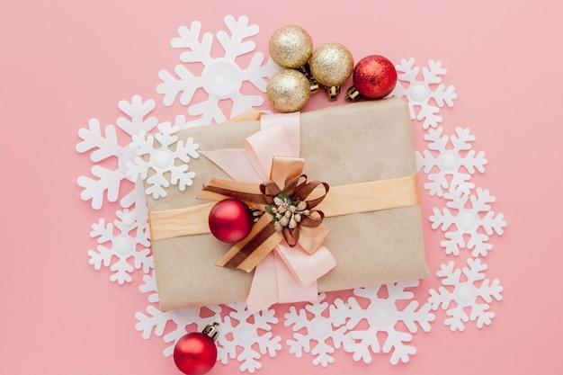 Schließen sie herauf schuss des kleinen geschenks, das mit band auf rosa eingewickelt wird. weihnachten minimal. flach liegen. ansicht von oben Premium Fotos