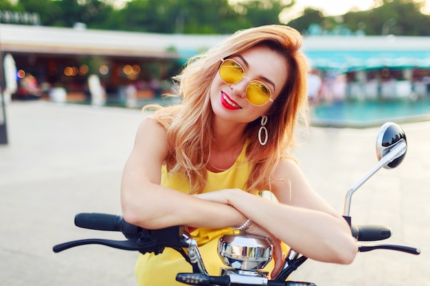 Schließen sie herauf sommerporträt der fröhlichen rothaarigen frau in der stilvollen gelben sonnenbrille, die elektroroller in der sonnigen modernen stadt reitet. trendige accessoires. Kostenlose Fotos