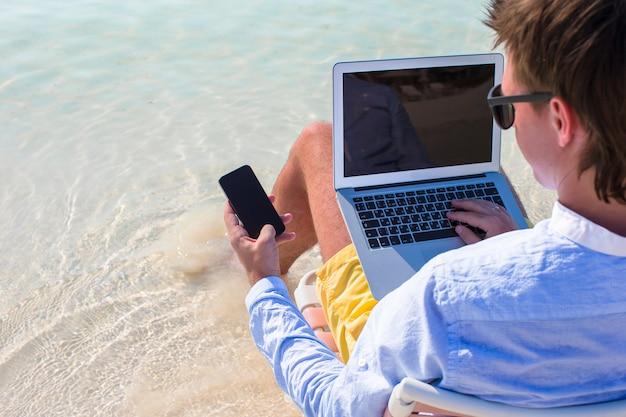 Schließen sie herauf telefon auf hintergrund des computers am strand Premium Fotos