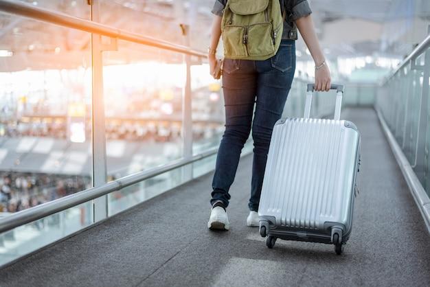 Schließen sie herauf unteren körper des frauenreisenden mit gepäckkoffer, der auf der ganzen welt geht Premium Fotos