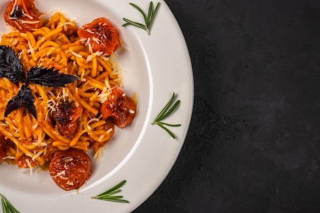 Schließen sie nah pasta mit kirschtomaten, käse und rosmarin, die auf platte auf dunklem strukturiertem hintergrund serviert werden Premium Fotos