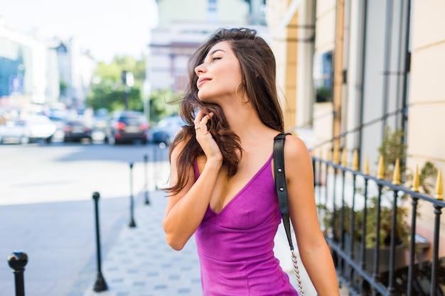 Schließen sie nahes atemberaubendes mädchen, das auf sonniger straße geht, sonniges wetter genießt, einkaufen, freunde wartet, um am wochenende tolle zeit zu haben. wellenförmige frisur. lila samt sexy kleid. romantische stimmung. Kostenlose Fotos