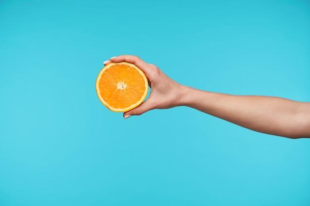 Schließen sie oben auf eleganter hübscher hand, die hälfte der frischen orange hält Kostenlose Fotos