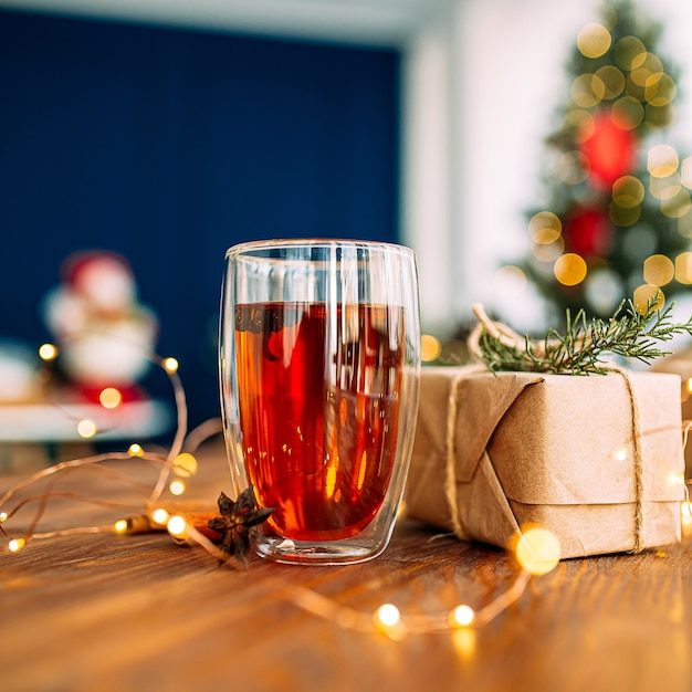 Schließen sie oben auf glasbecher schwarzen tees mit sternanis auf dem hölzernen festlichen tisch mit girlandenlichtern Premium Fotos