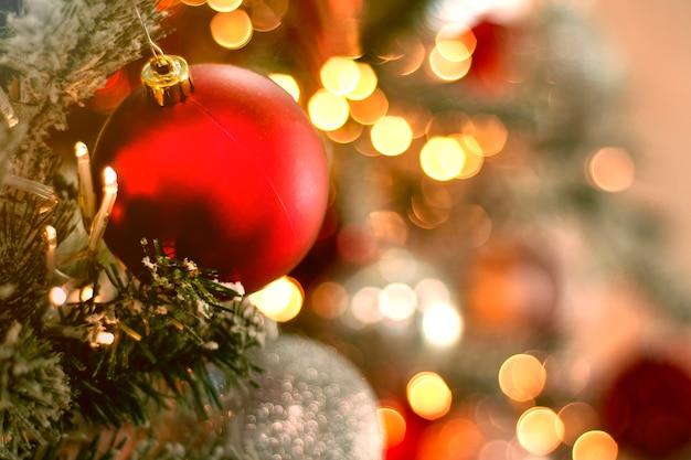 Schließen sie oben auf rotem ball auf weihnachtsbaum mit verschwommenen lichtern Premium Fotos