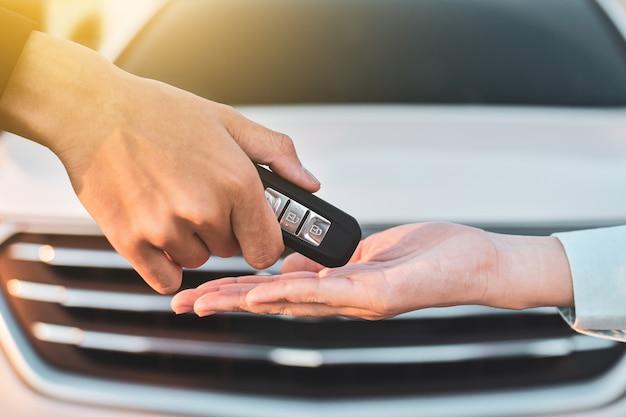 Schließen sie oben hand, die schlüsselverkaufsautokonzept hält, schlüsselauto geben und nehmen Premium Fotos