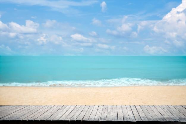 Schließen sie oben hölzerne tischplatte auf sandstrand blaues meer und tropischen strand, sommerferienkonzept. Premium Fotos