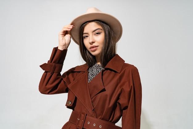 Schließen sie oben innenstudio-modeporträt der herrlichen frau im stilvollen winterbraunen mantel und im schwarzen hut Kostenlose Fotos