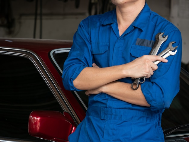 Schließen sie oben vom automechaniker in den einheitlichen haltenen werkzeugen oder in den schlüsseln in der garage. Premium Fotos