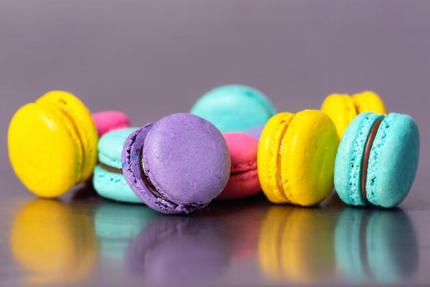 Schließen sie oben vom bunten macarons nachtisch auf purpurrotem hintergrund. Premium Fotos