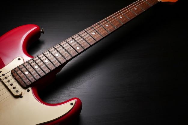 Schließen sie oben vom e-gitarrenkörper- und stutzendetail über schwarzen hintergrund. Premium Fotos