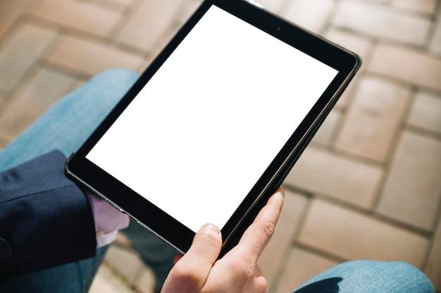 Schließen sie oben vom geschäftsmann unter verwendung der tablette draußen Kostenlose Fotos