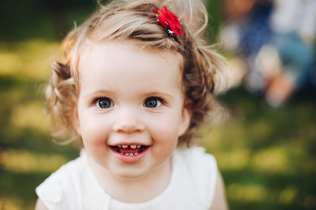 Schließen sie oben vom gesicht des lächelnden schönen babymädchens auf natursommer beim aufstellen an der kamera Kostenlose Fotos