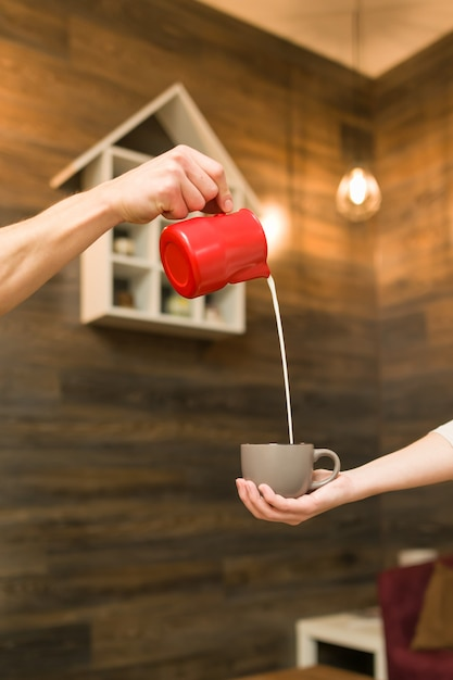 Schließen sie oben vom gießen der gedämpften milch in kaffeetasse Premium Fotos