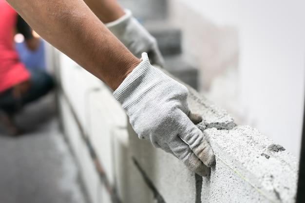 Schließen sie oben vom industriellen maurer, der ziegelsteine auf baustelle, errichtende wände installiert. Premium Fotos