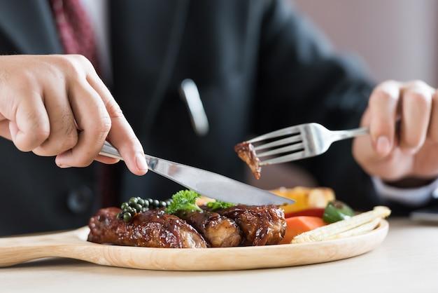 Schließen sie oben vom jungen geschäftsmann, der rippensteak auf hölzernem behälter am restaurant isst. Premium Fotos