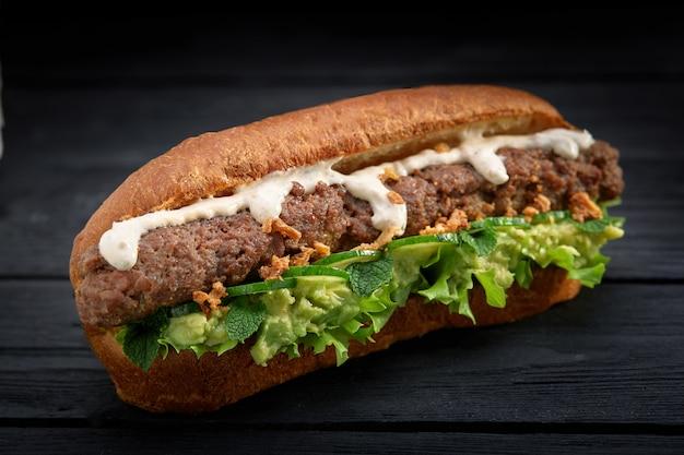 Schließen sie oben vom kebabsandwich auf schwarzem hölzernem hintergrund Premium Fotos