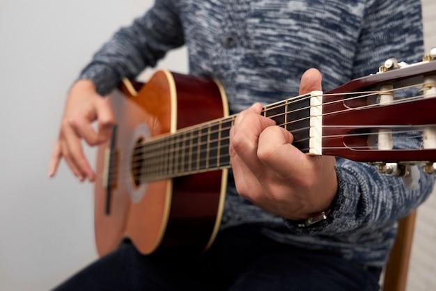 Schließen sie oben vom mann, der akustikgitarre spielt. Premium Fotos