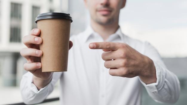 Schließen sie oben vom mann, der auf kaffee zeigt Kostenlose Fotos