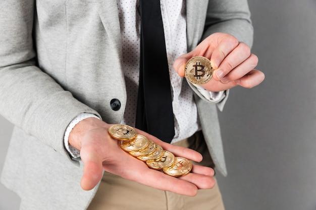 Schließen sie oben vom mann, der stapel goldene bitcoins hält Kostenlose Fotos