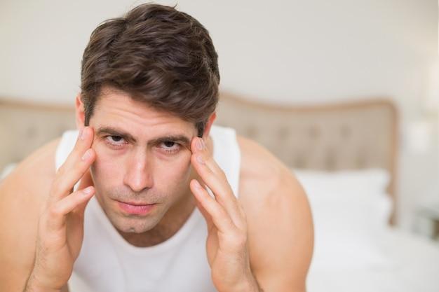 Schließen sie oben vom mann, der unter kopfschmerzen im bett leidet Premium Fotos